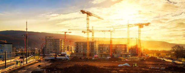 Large construction site including several cranes, with lots of gold sunlight stock photo
