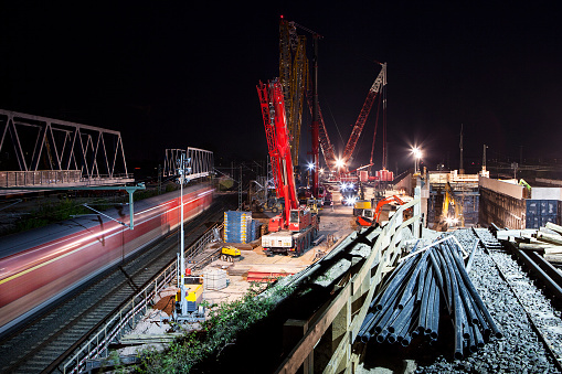 Large construction site at dusk, railway track and passing suburban train, long exposure