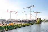 Large construction site with many cranes on a river, on a sunny, hazy day - Berlin 2018
