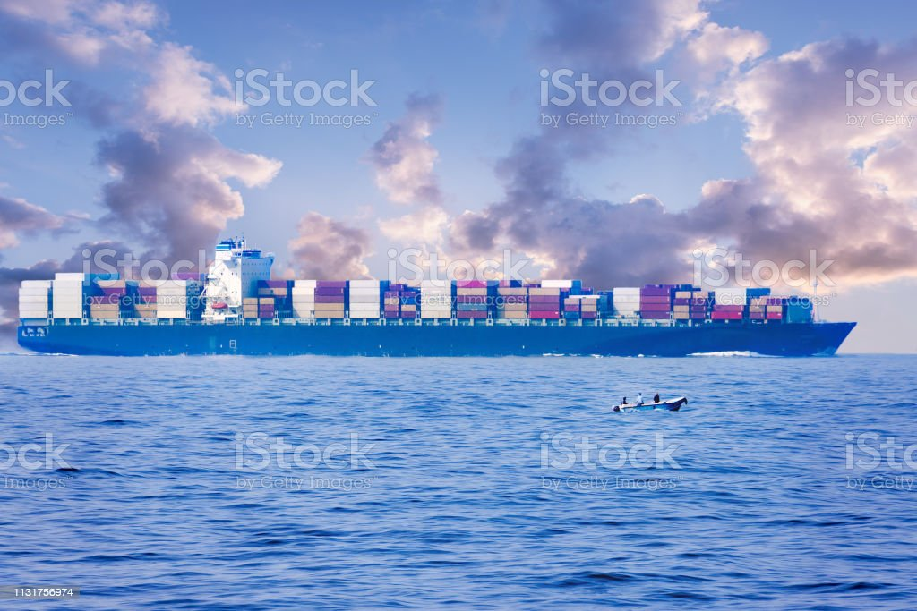Large container cargo ship in the ocean, side view. Small fishing...