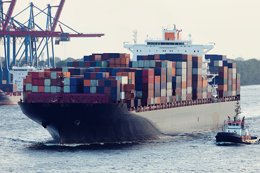 Large Container Ship Assisted By Tugboat in Hamburg Harbour