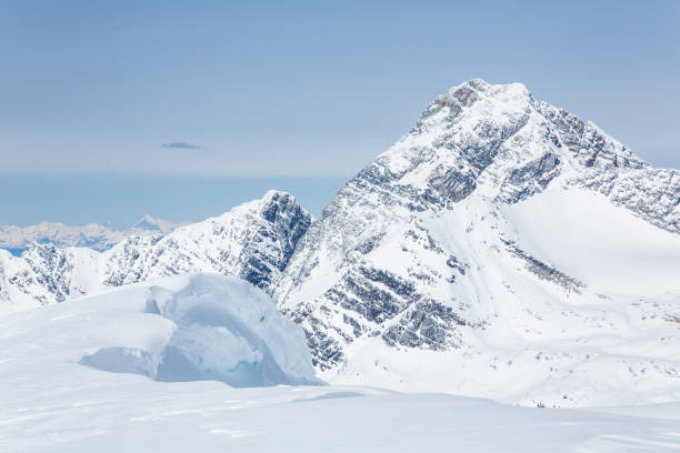 large cornice of overhanging snow from youngs peak looking up at mount sir donald - british columbia glacier national park stock pictures, royalty-free photos & images