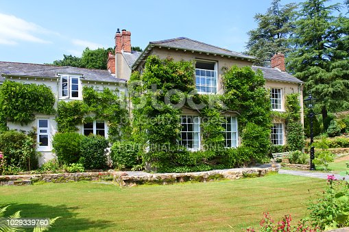 Netherbury, Dorset, UK - July 02, 2018: Large country house with climbing wisteria and roses. This type of real estate is much sought after in rural England.