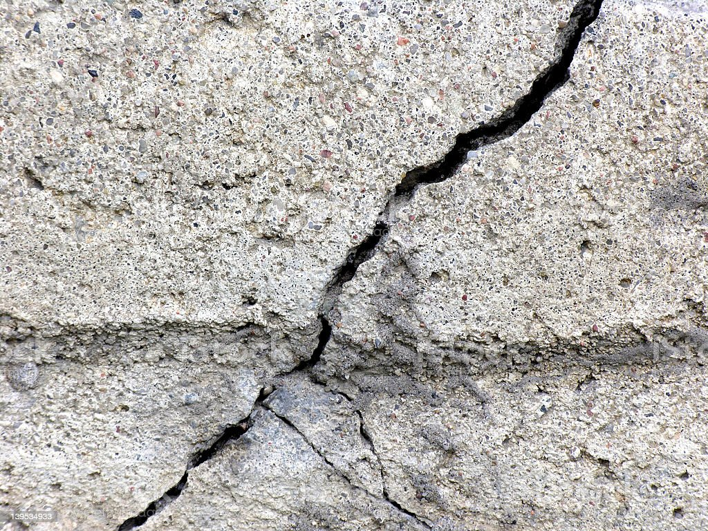 A large crack in gray concrete royalty-free stock photo