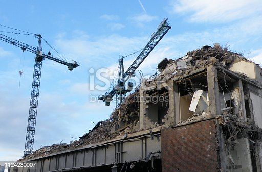 large cranes over a large concrete building being demolished with exposed walls during redevelopment of a large urban site