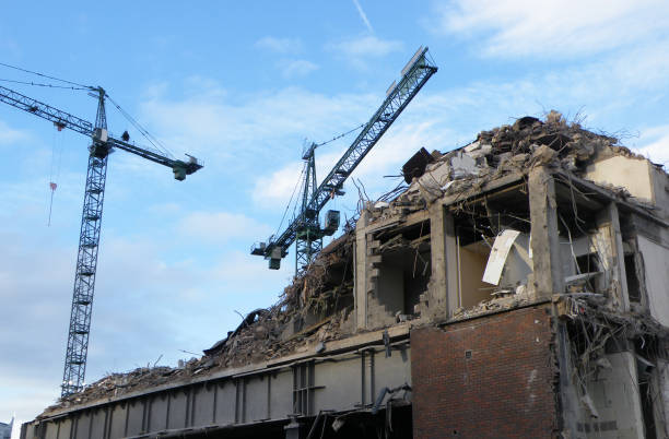 large cranes over a large concrete building being demolished with exposed walls during redevelopment of a large urban site large cranes over a large concrete building being demolished with exposed walls during redevelopment of a large urban site collapsing stock pictures, royalty-free photos & images