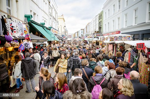 London, England - November 2, 2013: a large crowd of people flocking Portobello Road in London. Portobello Road is famous for its market, where you can find many vintage occasions.