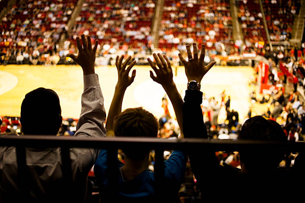 large crowd people attend a sports event. stadium. basketball court. - fan enthusiast stock photos and pictures