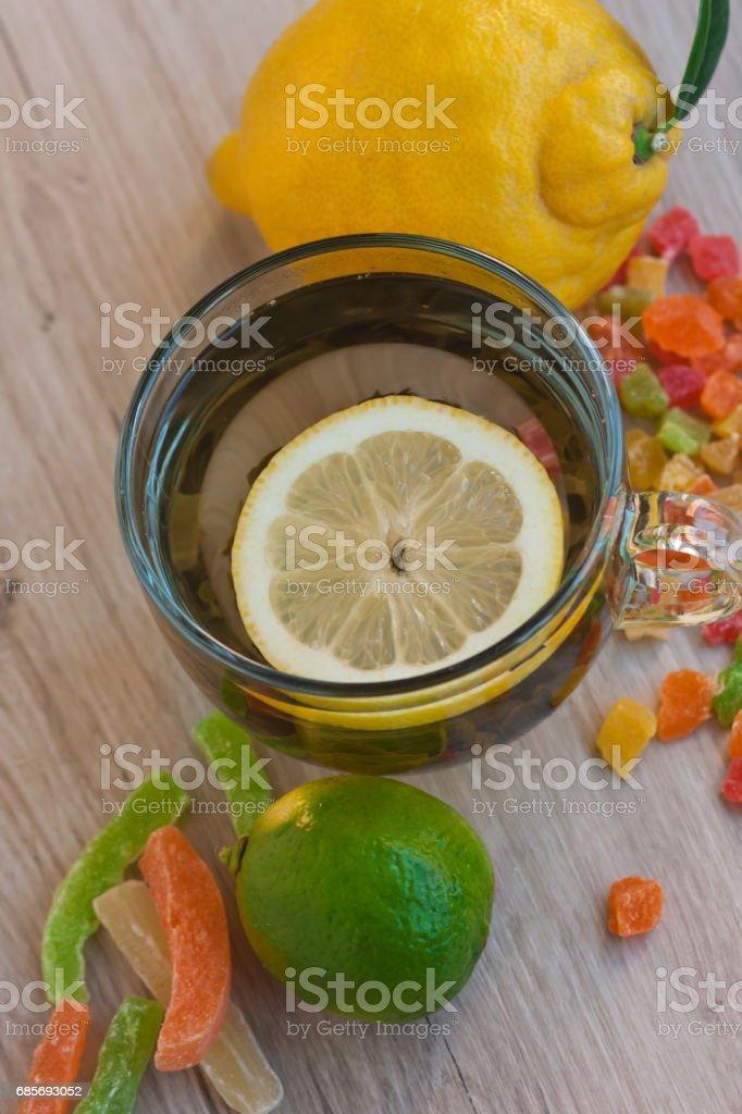 과일 차, 큰 노란 레몬, 잘 익은 신선한 라임 큰 컵, 작은 설탕에 절인 과일 royalty-free 스톡 사진