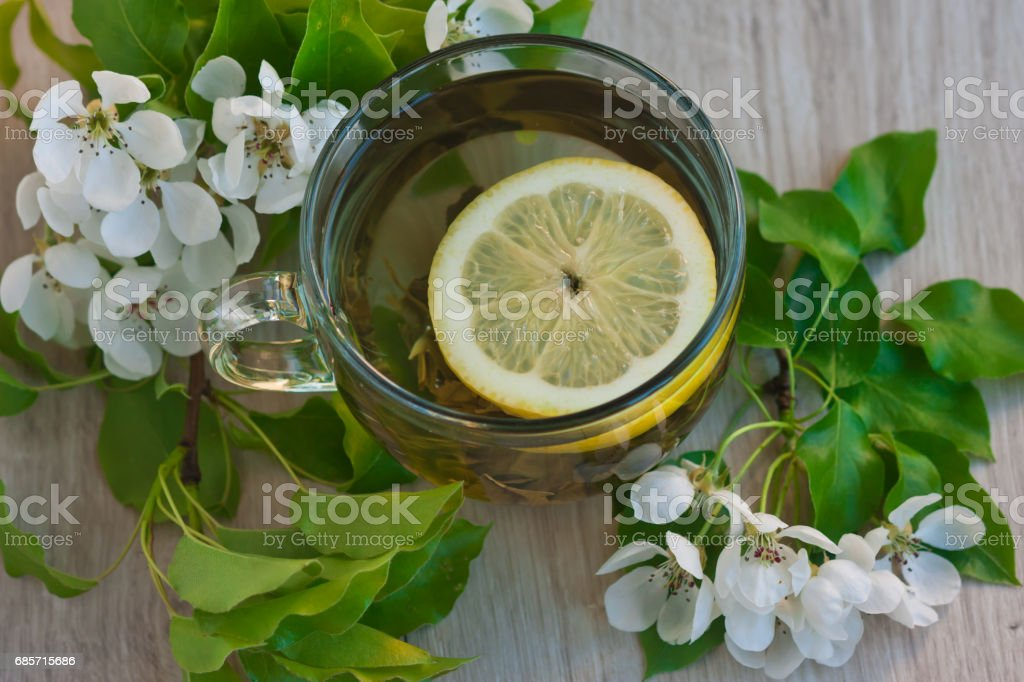 A large cup of fruit tea with a lemon and a flowering branch near royalty-free stock photo