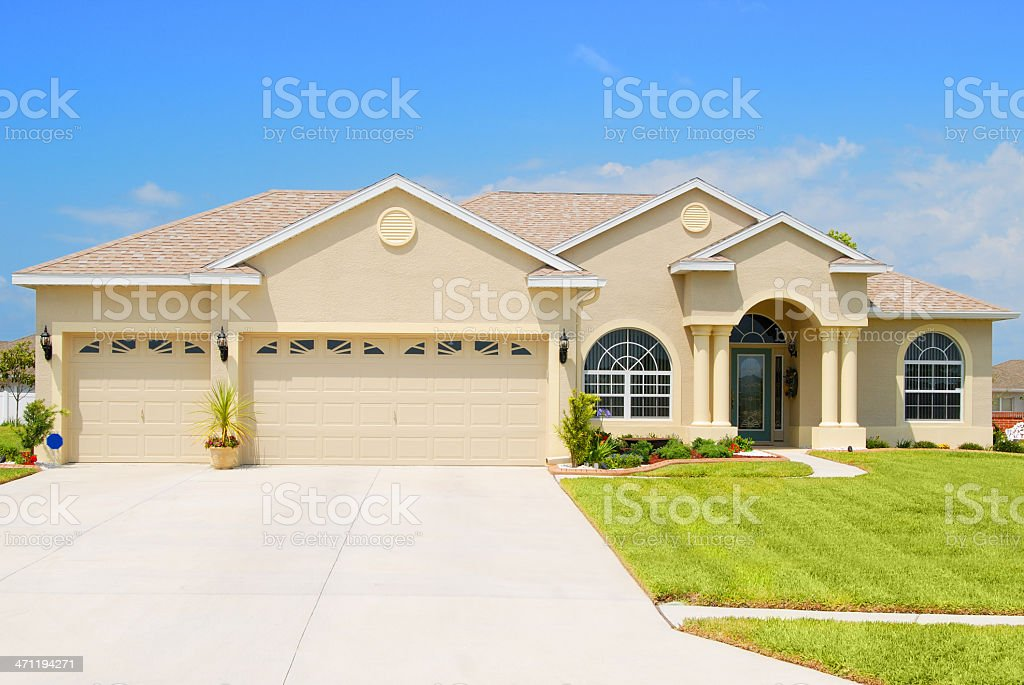 Large custom home with beige exterior and green lawn stock photo