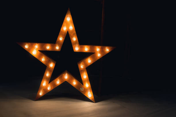 large decorative retro star with lots of burning lights on grunge concrete background - celebrities stock pictures, royalty-free photos & images