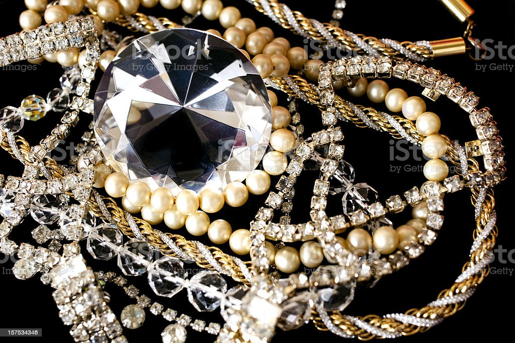 Large diamond with other jewlery on black background.. royalty-free stock photo