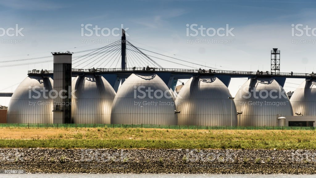 Large digestion towers for the treatment of wastewater at the edge of the port stock photo
