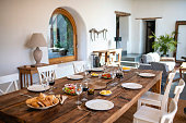 Unoccupied Spanish farmhouse dining table set for six people with bread, salads, condiments, and red wine.