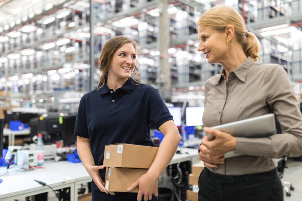 Large distribution company employees walking together Female worker holding packages talking with warehouse manager and smiling. Large distribution company employees walking together and talking. foreman stock pictures, royalty-free photos & images