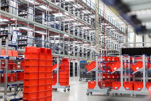 Interior of large distribution warehouse with movement trolleys and shelves.