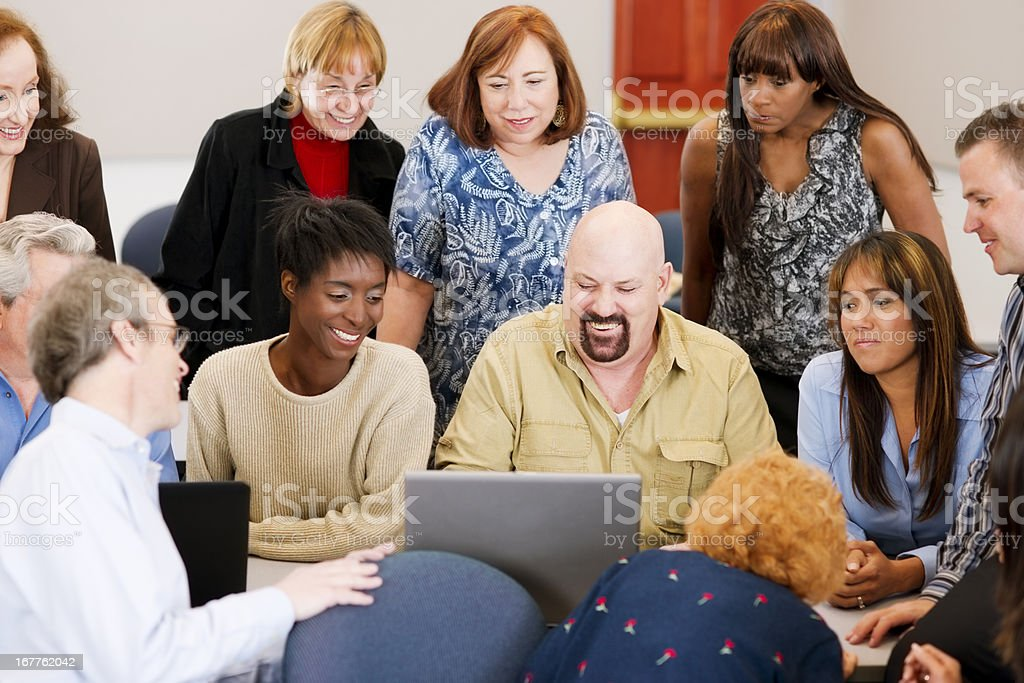 Large diverse group in front of a laptop royalty-free stock photo