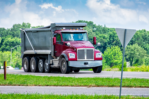 Horizontal shot of a large dump truck delivering gravel to a commercial construction site.