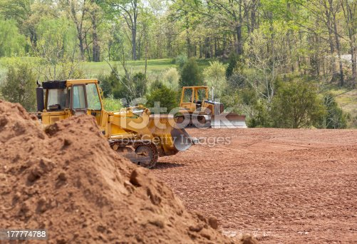 Land being levelled and cleared by yellow earth moving digger