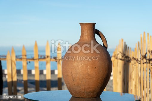 Large earthenware jug stands on a table on the shore near the sea water in Batumi, Georgia. Close up