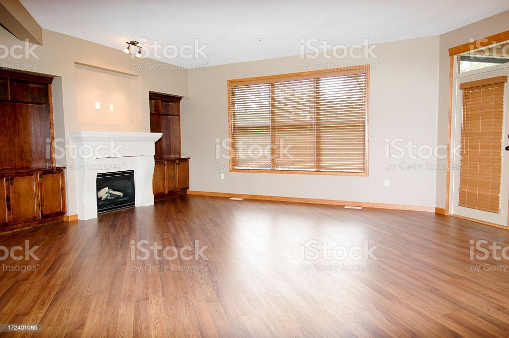 Large empty room with fireplace and wood flooring stock photo