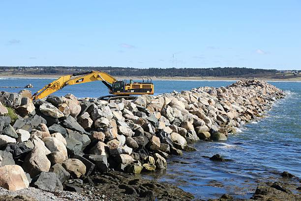 Large excavator used in the building of a breakwater Cape Saint Mary, Canada - October 16, 2015: Large ecavator used in the building of a beakwater at Cape Saint Mary, Nova Scotia, Canada. Before the building of the breakwater the ocean currents caused problems for fishing boats tied at the wharf there.  Lots of very large rocks groyne stock pictures, royalty-free photos & images