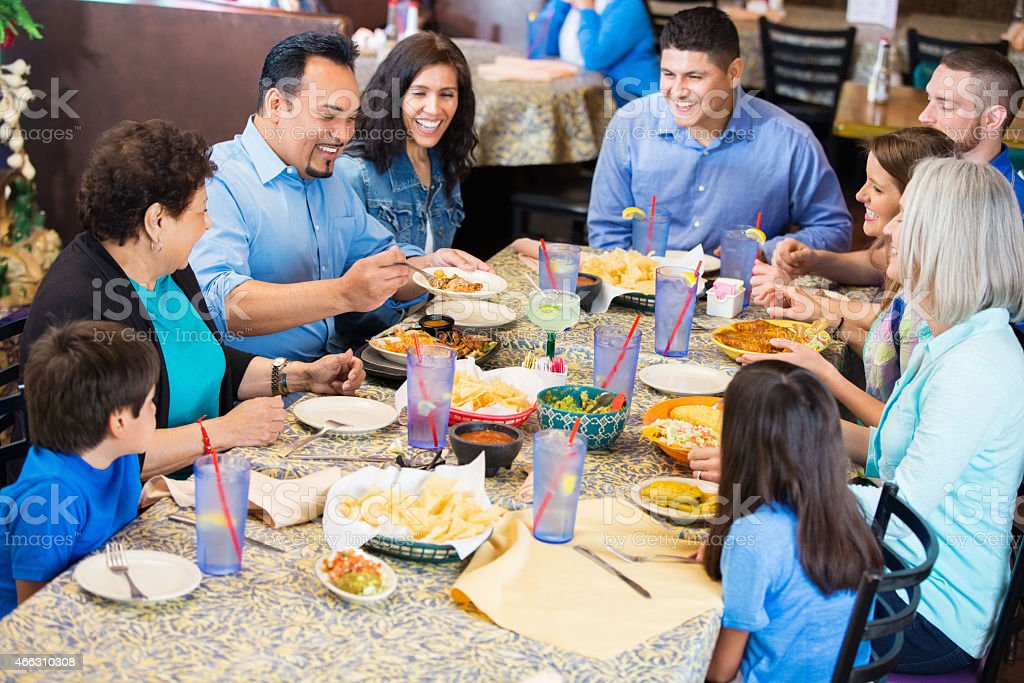 Large extended family having meal together in Mexican restaurant stock photo