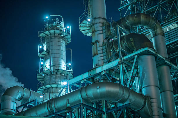 large factory detail at night - refinery stock photos and pictures