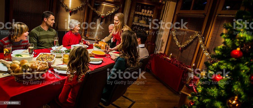 Mid adult woman serving roasted turkey at Christmas dinner.