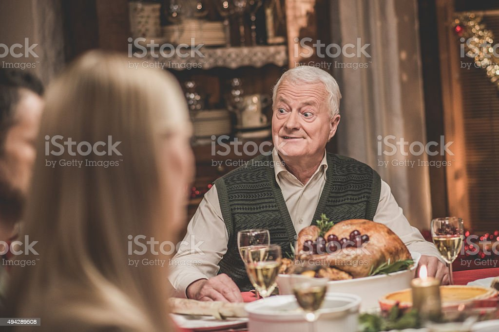 Grandfather making face at Christmas dinner.
