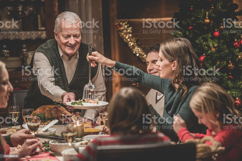Grandparents with family at Christmas dinner.