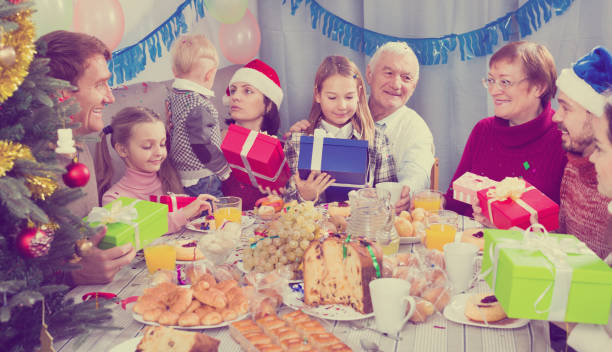 Large family handing gifts to each other stock photo