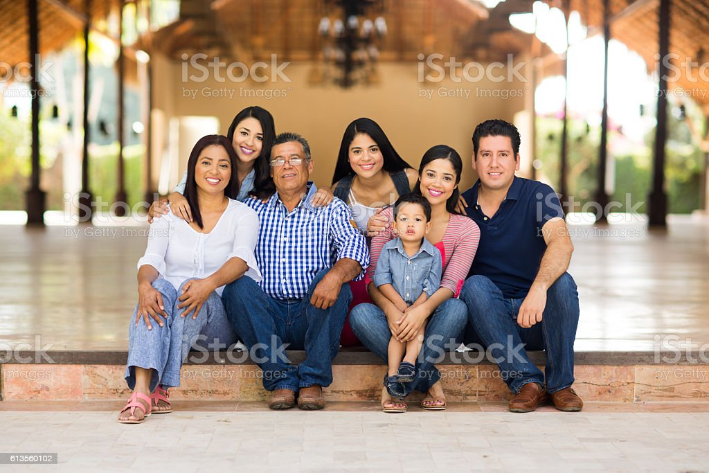 Large family sitting and smiling at the camera stock photo