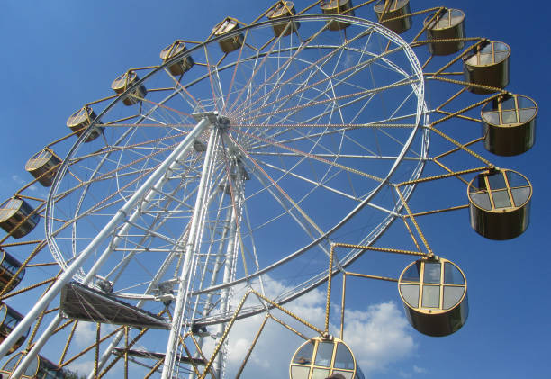 Large ferris wheel with cabins on a summer day against the blue sky stock photo
