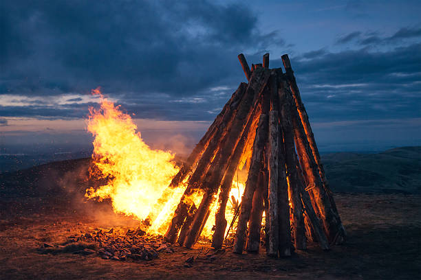 Large fire beacon burning on hilltop Flames and sparks from a large fire on a rural hilltop, lighting up the sky at twilight. beacon stock pictures, royalty-free photos & images