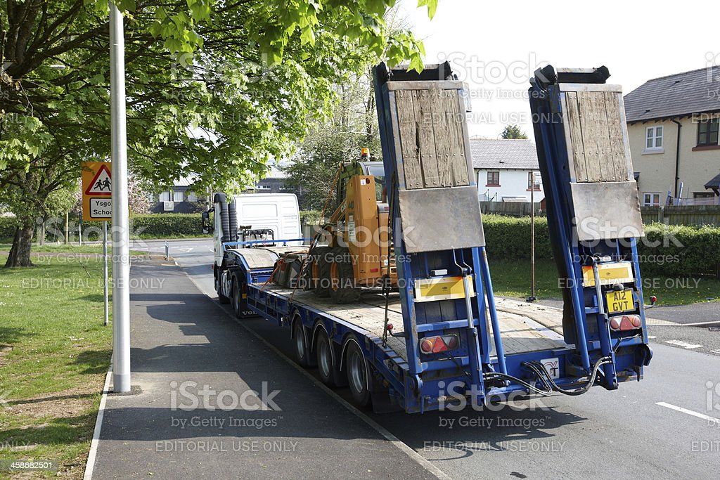 Large flatback semi with mechanical bulldozer aboard royalty-free stock photo