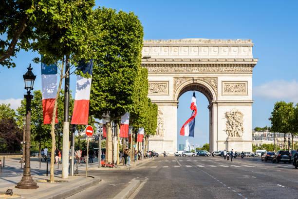 Un grand drapeau français flotte sous l'Arc de Triomphe à Paris, France. - Photo