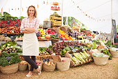 Female Stall Holder At Farmers Fresh Food Market, Strading And Smiling To Camera