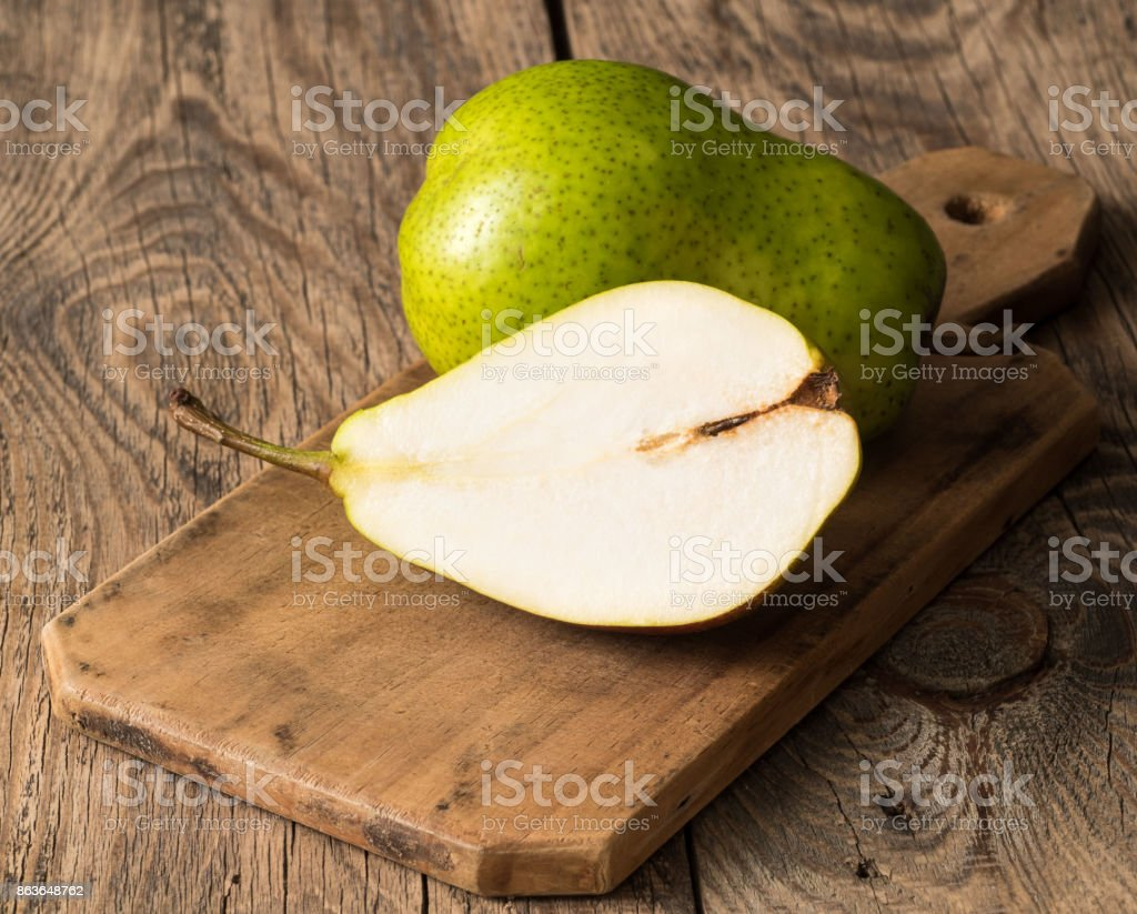 large fresh green pear and a half on a cutting Board on a wooden table. Side view stock photo