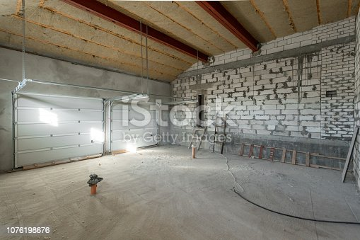 534196421 istock photo Large garage for two cars with of the gate. overhaul and reconstruction. Working process of warming inside part of roof. House or apartment is under construction, remodeling, renovation, restoration. 1076198676
