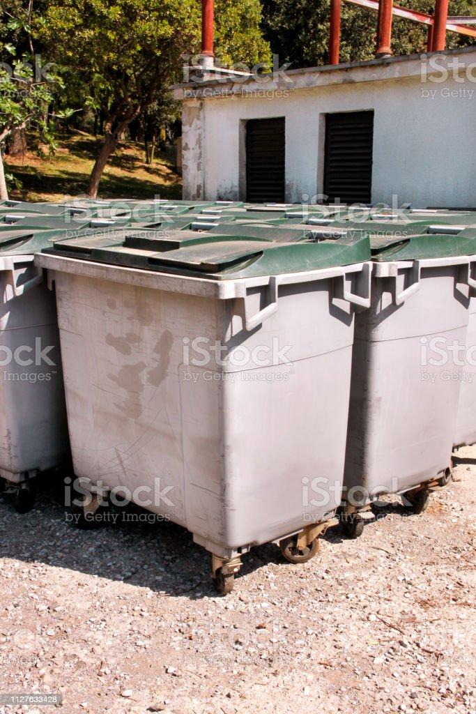Recipientes de lixo grandes, contentores de lixo e lixeiras em pé na fila. Ordenada estiva latas de lixo pronto para coleta de lixo separado. Recipientes de lixo ambientalmente amigável, reciclar caixas, tanques. - foto de acervo