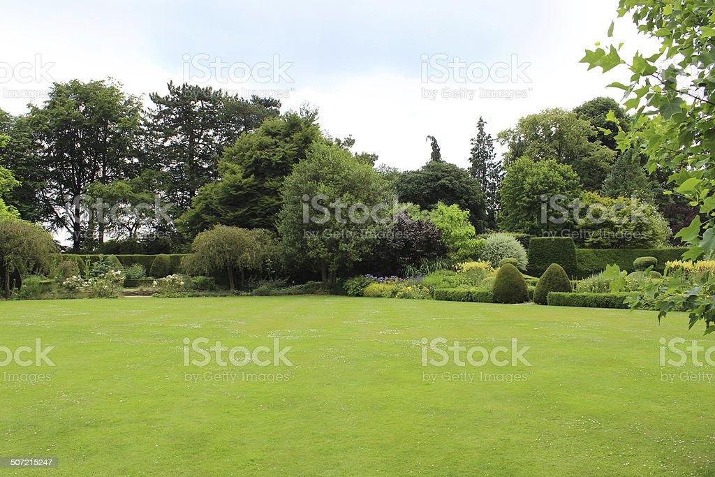 Amplio espacio con césped del jardín turf como bowling green, flores, árboles, arbustos autóctonos - foto de stock