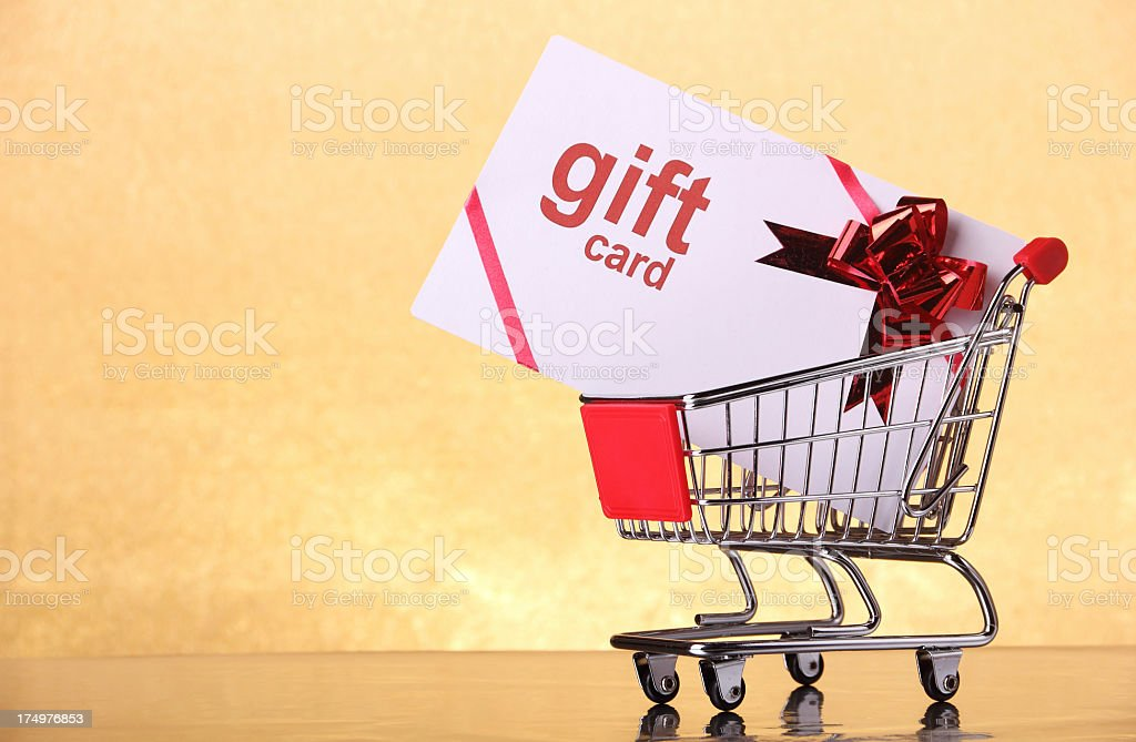 A large gift card in a shopping cart on a peach background stock photo