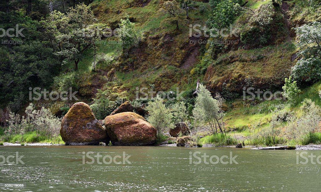 large golden boulders on rugged river bank stock photo