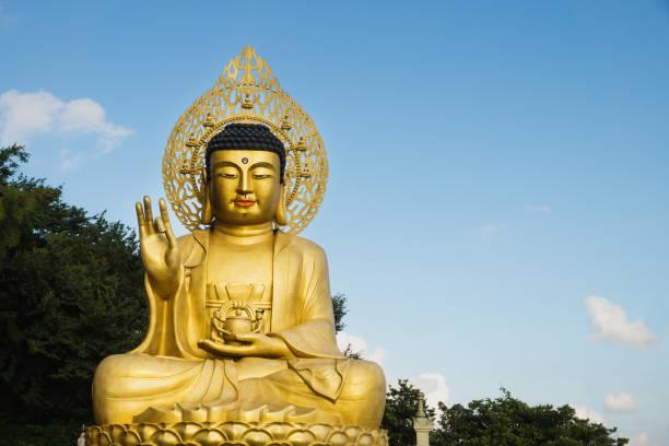 Large golden Buddha statue at Sanbanggulsa temple, Sanbang-ro, Jeju Island, South Korea Large golden Buddha statue in the last sunlight at Sanbanggulsa temple, Sanbang-ro, Jeju Island, South Korea taoism stock pictures, royalty-free photos & images