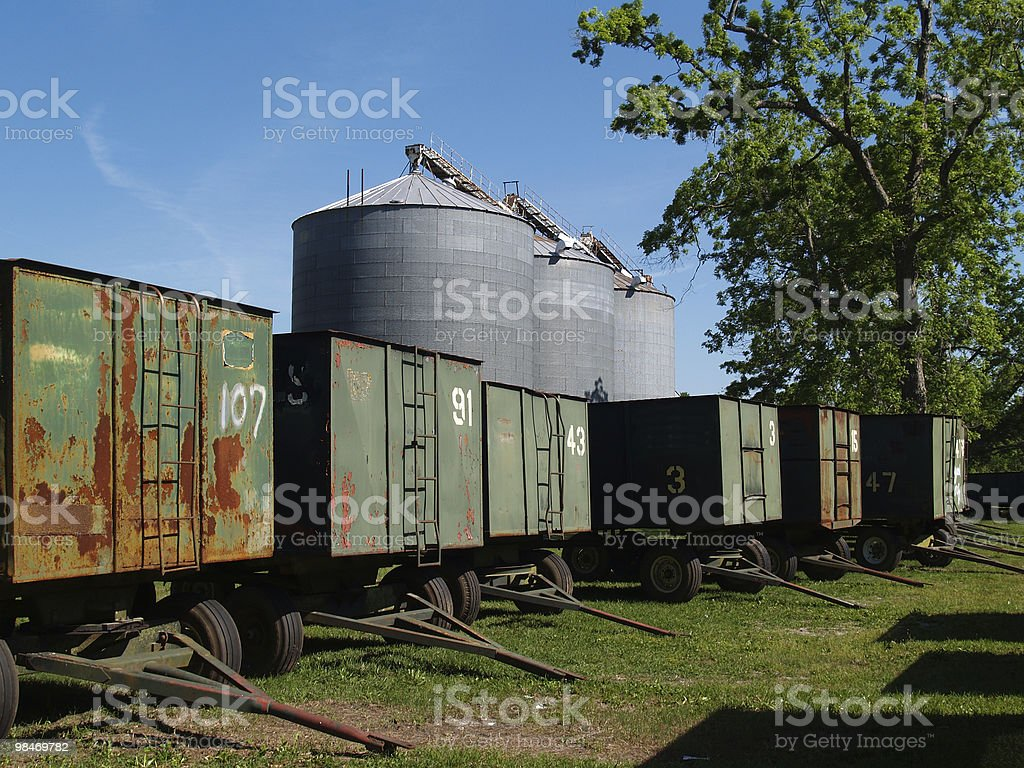 Large Grain Silos behind Wagons and a Pecan Grove royalty-free stock photo