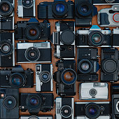 Large group of 35mm vintage film cameras lying in arrangement close to each other as a background