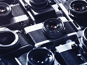 Close-up image of a large group of vintage film cameras lying in arrangement close to each other