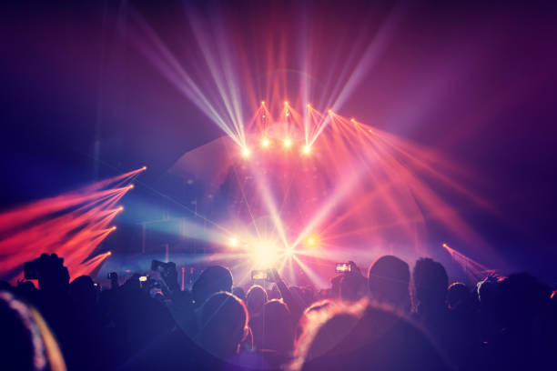 Large group of a happy young people enjoying concert Large group of a happy young people enjoying concert, having fun spending time in a night club, dancing in bright laser beams, men partying, celebrating holidays performance stock pictures, royalty-free photos & images